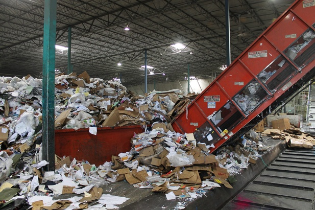 Massive piles of recyclables are processed by heavy equipment and trained staff